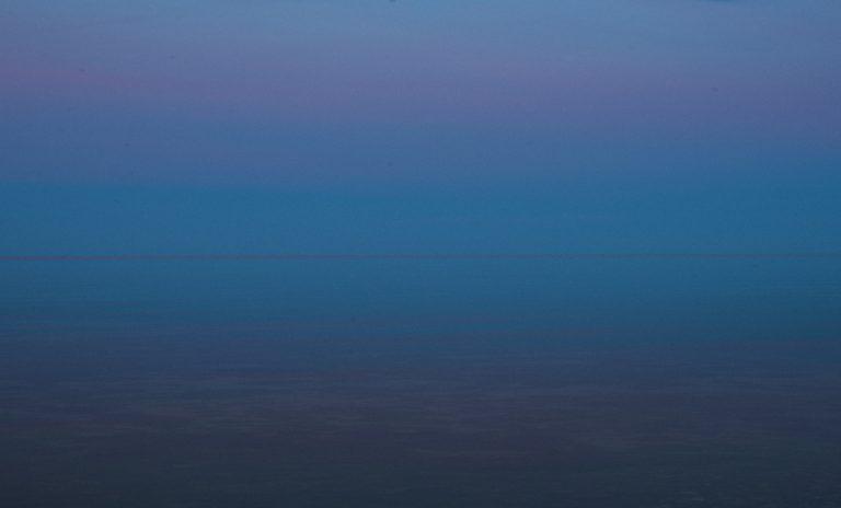 Windstille. Das Meer ist glatt und spiegelt die horizontnahen Himmelsteile. Das Spiegelbild ist dunkler, weil ein Teil des Lichts ins Wasser eindringt und absorbiert wird.