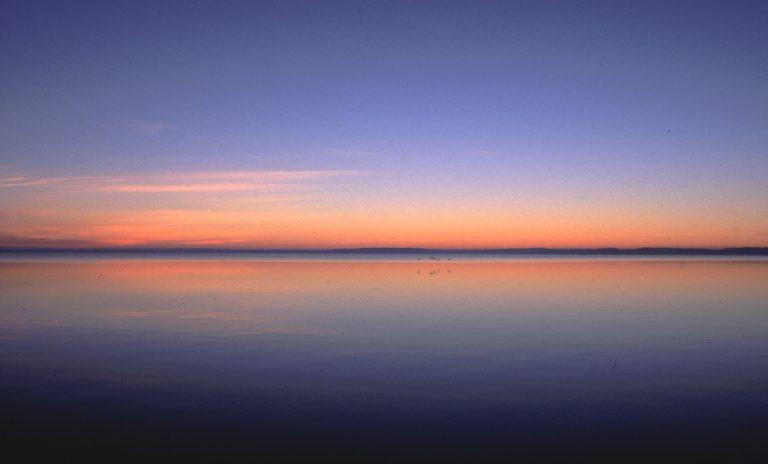Es ist windstill. Die Meeresoberfläche ist ein perfekter Spiegel. Nur in der Ferne kräuseln sich Wellen und erzeugen einen blauen Streifen.