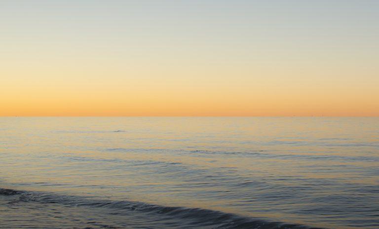 Die uns zugewandten Wellenflanken spiegeln den dunkelblauen oberen Himmel, die flachen Teile den orange Horizontalstreifen.