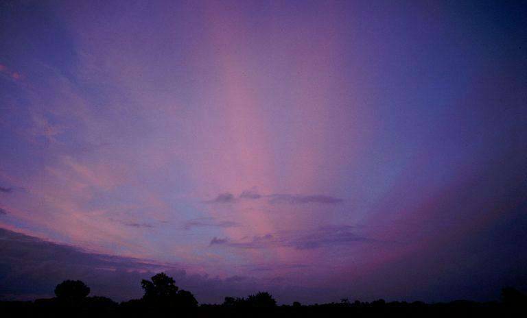 Diese zarten rosa Gebilde sind keine Lichtstrahlen, sondern von der Abendsonne beleuchtete, parallel über den Himmel gezogene Cirruswolken.