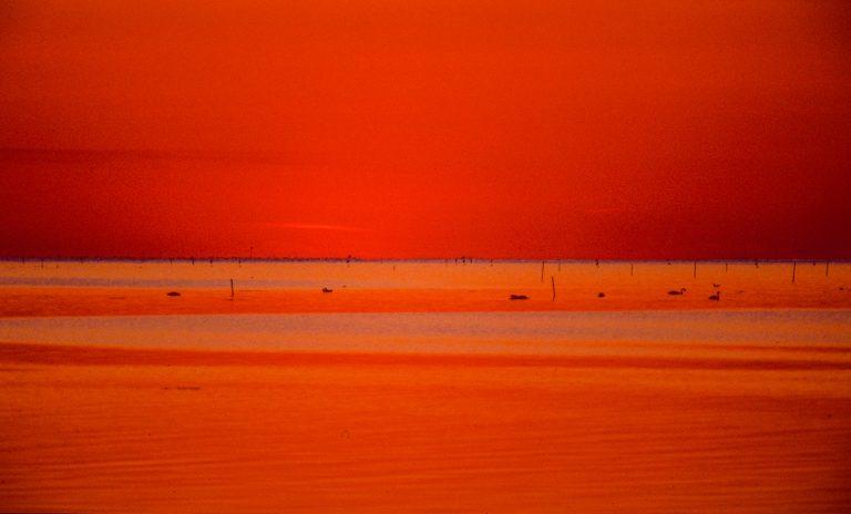 Aufnahme mit Teleobjektiv. In den orange Flächen sind die Wellen höher und stiler. Sie spiegeln auch höhere Teile des Himmels.