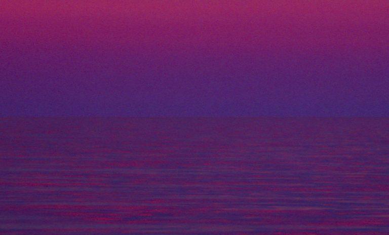 Blick nach Osten. Eine dunkle Wolkenwand wird intensiv vom Gegenabendrot gefärbt. Darunter derdunkel blaue Erdschatten. Die Wellen vermischen Rot und Blau zu Violett.