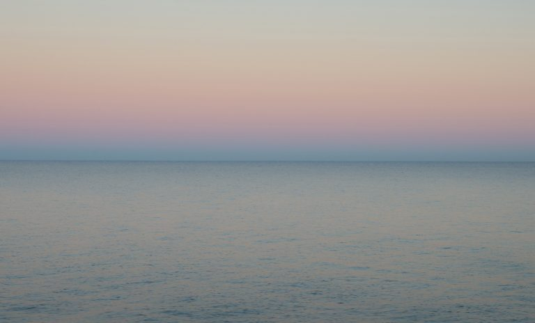 Blick nach Osten etwa 10 Minuten nach Sonnenuntergang. Der blaue Erdschatten schiebt sich vor das Gegenabendrot. Die Wellen spiegeln je nach Neigung Rosa oder Blau.