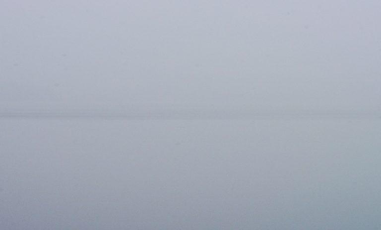 Das Meer ist spiegelglatt. Nur am Horizont ist die Wasserfläche gekräuselt und sorgt für den dunklen Streifen.