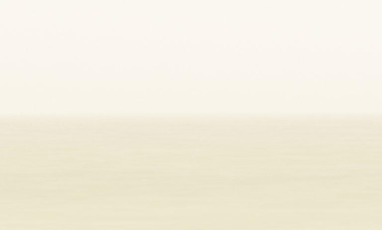 Blick in Richtung der vom Nebel verhüllten Abendsonne. Diese hüllt den Nebel in ein warmes gelbliches Licht.