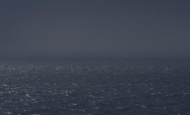 Der Himmel ist gleichmäßig grau. Die Sonne dringt mit schwachem Licht durch die Wolkendecke und erzeugt unzählige Reflexe auf dem Wasser.