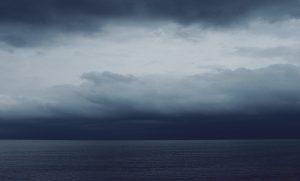 Die Wellen in Horizontnähe spiegeln den hellen oberen Teil des Himmels zu uns. Das Meer erscheint heller als die niedrige Wolkenschicht.