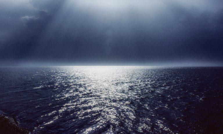 Das Sonnenlicht bricht durch einzelne Wolkenlücken und erzeugt im Wechselspiel mit den Wellen ein glitzerndes Band.