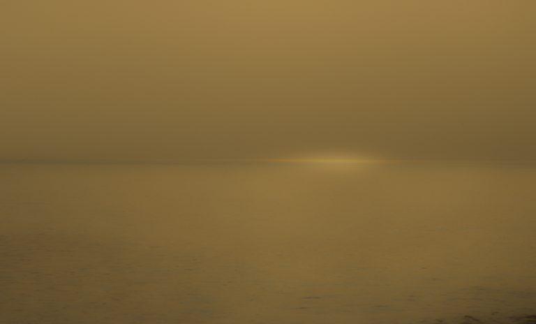Das gelbe Licht der tiefstehenden Abendsonne verleiht dem Nebel einen goldenen Schein.