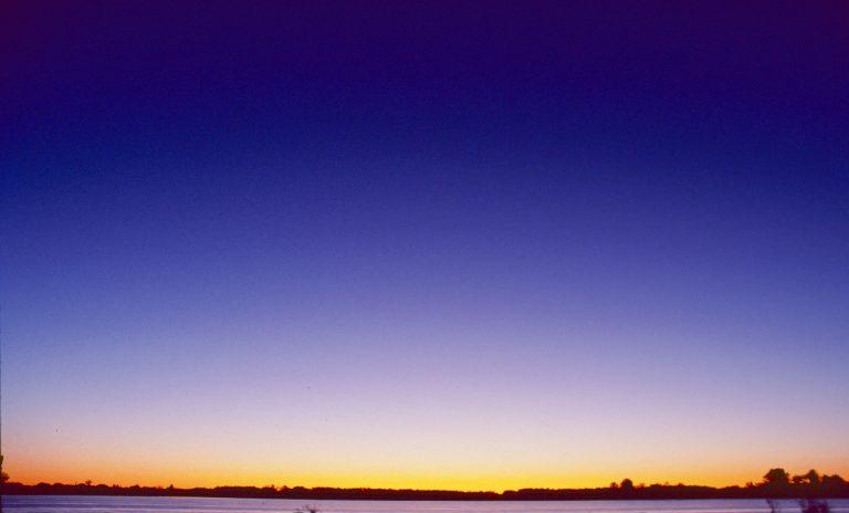 Der horizontale Streifen: Lange vor Sonnenuntergang leuchtet der Horizont in Sonnennähe gelb oder orange