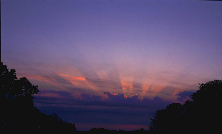 Auch die Licht- und Schattenstrahlen, die sich nach oben im Dunst abzeichnen, sind in Wirklichkeit parallel.