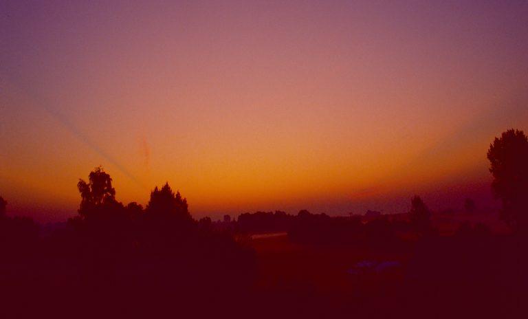 """Die Schatten zweier Wolken ziehen sich wie zwei """"Dunkelstrahlen"""" über den Abendhimmel."""