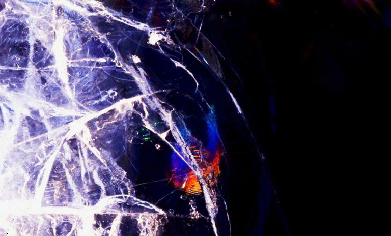 Risse in der Eisdecke eines Sees leuchten im Sonnenlicht ähnlich wie Seifenblasen