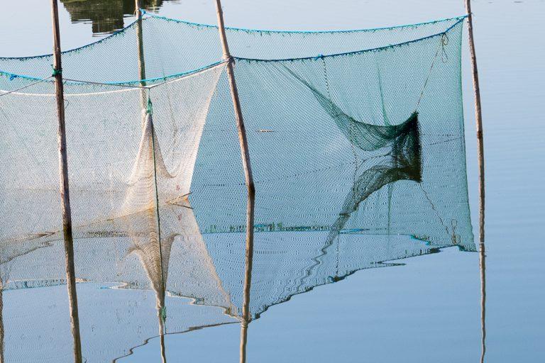 Ein Fischernetz spiegelt sich im Wasser.